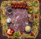 Ingredients for cooking homemade pasta with tomatoes on a branch, spices, peppers and cheese place for text,frame on wooden rustic Royalty Free Stock Images