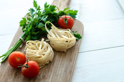 Ingredients for cooking Italian pasta - spaghetti, tomatoes, basil and garlic. Stock Image