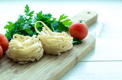 Ingredients for cooking Italian pasta - spaghetti, tomatoes, basil and garlic. Stock Photography