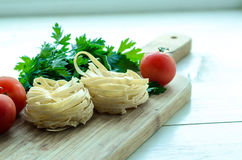 Ingredients for cooking Italian pasta - spaghetti, tomatoes, basil and garlic. Royalty Free Stock Image