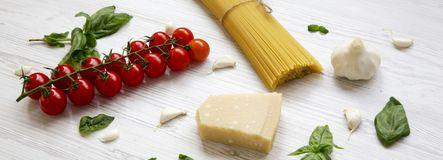 Ingredients for cooking italian pasta on a white wooden surface, low angle view. Close-up stock photo