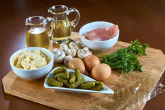 Ingredients for cooking jellied chicken with mushrooms pickled cucumber lettuce Stock Image