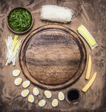 Ingredients for cooking Korean food glass noodles, chuka seaweed, boiled quail eggs, ginger, corn  laid out around  cutting board Stock Images