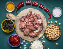 Ingredients for cooking lamb canned chickpeas condiment hot red pepper tomato paste prunes sliced onions on a cutting board on woo Royalty Free Stock Photo
