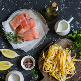 Ingredients for cooking lunch - raw salmon, dry pasta tagliatelle, cream, olive oil, spices and herbs. On a dark background. Top view Royalty Free Stock Photography