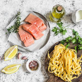 Ingredients for cooking lunch - raw salmon, dry pasta tagliatelle, cream, olive oil, spices and herbs. On a light background. Top view Royalty Free Stock Images