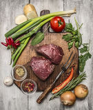 Ingredients for cooking meat beef steaks with autumn vegetables and seasonings on wooden cutting board on bright, rustic wood back Royalty Free Stock Images