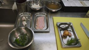 Ingredients for cooking are on the metal table of the chef. Onions, dill, rice and fresh duck meat are on the chef`s stock video