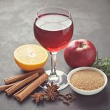Ingredients for cooking mulled wine: glass of red wine, fruits, cinnamon sticks, star anise, sugar, herbs. Concept of hot fall or winter drinks Royalty Free Stock Image