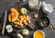 Ingredients for cooking  nut milk oatmeal with pumpkin, apples and honey on wooden brown background Royalty Free Stock Image