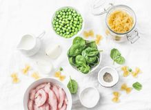 Ingredients for cooking one pot creamy chicken spinach and green peas farfalle pasta on white background, top view. stock photo