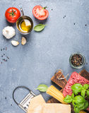 Ingredients for cooking pasta Bolognese. Spaghetti, Parmesan cheese,  tomatoes, metal grater, olive oil, garlic, minced Royalty Free Stock Photo