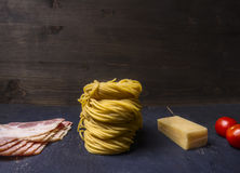 Ingredients for cooking pasta carbonara, raw pasta, bacon, cheese, cherry tomatoes  wooden rustic background close up Stock Images