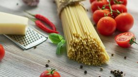 Ingredients for cooking pasta. Closeup of bunch of tied spaghetti on wooden table with ripe tomatoes and piece of cheese with condiments around stock video footage
