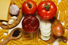 Ingredients for cooking pasta. Different raw ingredients: dry pasta, tomatoes, tomato and basil sauce, onion, garlic, pepper and parmesan cheese royalty free stock image
