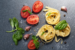Ingredients for cooking pasta. Italian tagliatelle pasta with tomato on black wooden background. Stock Images