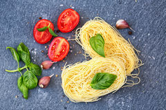Ingredients for cooking pasta. Italian tagliatelle pasta with tomato on black wooden background. Stock Photography