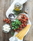 Ingredients for cooking pasta. Spaghetti, basil, cherry-tomatoes, mozarella, olive oil, thyme, salt, spices on rustic chopping boa Stock Photo