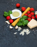 Ingredients for cooking pasta. Spaghetti, olive oil, garlic, Parmesan cheese, tomatoes and fresh basil on black slate Royalty Free Stock Images