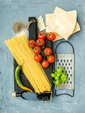 Ingredients for cooking pasta. Spaghetti, Parmesan cheese, cherry tomatoes, metal grater, olive oil and fresh basil on Stock Photography