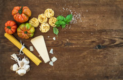 Ingredients for cooking pasta. Spaghetti, tagliatelle, garlic, Parmesan cheese, tomatoes and fresh basil on rustic Stock Photo