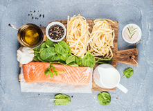 Ingredients for cooking pasta tagliatelle with salmon, spinach and cream Royalty Free Stock Photo