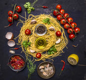 Ingredients for cooking pasta with tomato on a branch, oil, garlic and pepper, egg on wooden rustic background top view close up Royalty Free Stock Photography