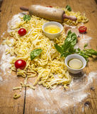 Ingredients for cooking pasta with tomato sauce, eggs ,rolling pin,flour ,olive oil, tomatoes, herbs on on rustic wooden backgroun Royalty Free Stock Photos