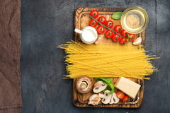 Ingredients for cooking pasta on wooden table with Italian spagh Royalty Free Stock Photo