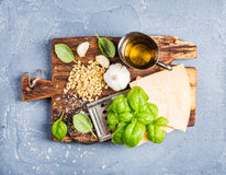 Ingredients for cooking Pesto sauce. Parmesan cheese, metal grater, fresh basil, olive oil, garlic and pine nuts on old. Rustic wooden board over grey concrete royalty free stock photo