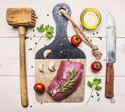 Ingredients for cooking  pork steak with herbs, garlic, meat hammer, a knife for meat, oil and herbs wooden rustic background t. Ingredients for cooking  pork Royalty Free Stock Photos