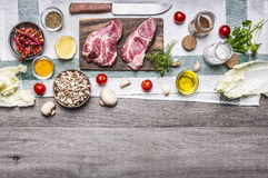 Ingredients for cooking pork steaks on the cutting board, on a napkin, vegetables, mushrooms, lettuce, spices and herbs on wooden Stock Image