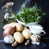 Ingredients for cooking potato soup with garlic, rukola, onions Royalty Free Stock Photos