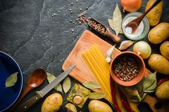 Ingredients for cooking: potatoes, salt, pepper, onion, garlic on a dark stone table. Royalty Free Stock Photos