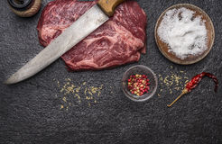 Ingredients for cooking raw beef steak with salt and pepper carving knife pepper mill dark rustic background top view horizon. Ingredients for cooking raw beef stock images
