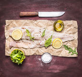Ingredients for cooking raw cod on peper knife lemon arugula lettuce salt oil rustic wooden background top view close up. Ingredients for cooking raw cod on Stock Photography