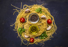 Ingredients for cooking raw homemade pasta with cherry tomatoes, parsley, pepper and butter on wooden rustic background top view c Royalty Free Stock Photography