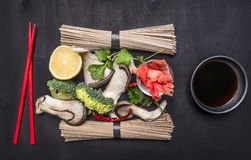Ingredients for cooking raw Japanese buckwheat noodles on wooden rustic background top view close up Stock Image
