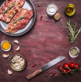 Ingredients for cooking raw lamb ribs in a pan with herbs, a knife, seasoning, tomatoes place for text,frame on wooden rustic back Royalty Free Stock Photography