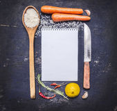 Ingredients for cooking rice with vegetables, a knife, a wooden spoon, lemon, spicy, pepper, garlic lined frame with  sheet of pap Stock Image