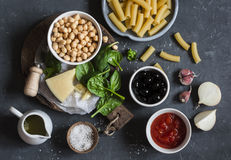 Ingredients for cooking rigatoni pasta with chickpeas, spinach and olives in a tomato sauce on a dark background, top view. Stock Image