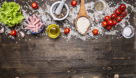 Ingredients for cooking risotto with ham, cheese, vegetables and spices and rice, wooden spoon, cherry tomatoes, oil salt bord Royalty Free Stock Images