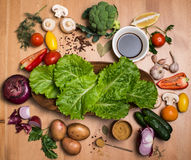 Ingredients for cooking on rustic wooden table around empty plat. E with salad leaves, round frame, top view. Fresh vegetables mushrooms greens and spices around Royalty Free Stock Photos