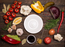 Ingredients for cooking on rustic wooden table around empty whit. E plate saucer, round frame, top view. Fresh vegetables greens and spices around free copy Stock Photos