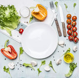 Ingredients for cooking salad cherry tomatoes, lettuce, peppers, spices oil  laid out around  white plate wooden rustic ba Royalty Free Stock Images