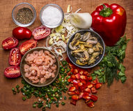 Ingredients for cooking seafood shrimp and mussels cherry tomatoes seasoning salt chopped red pepper chopped onion parsley on wood Stock Image