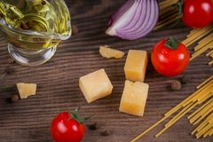Ingredients for cooking spaghetti - raw pasta, tomato, olive oil, spices, herbs stock photo