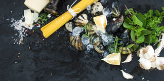 Ingredients for cooking Spaghetti vongole. Clams on chipped ice, raw pasta, Parmesan cheese, garlic, parsley and lemon Stock Photo
