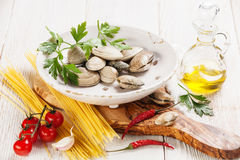 Ingredients for cooking spaghetti vongole. Shells vongole, raw sapaghetti, parsley leaves, cherry tomatoes royalty free stock images
