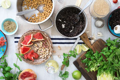 Ingredients for cooking tasty and healthy vegetarian food. On a white wooden table, top view. Black and white quinoa, chickpeas, grapefruit, mint, nuts, cabbage Royalty Free Stock Image